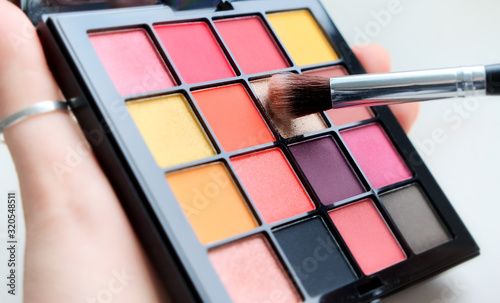 Close up a palette with colorful eye shadows and a makeup brush Fototapeta