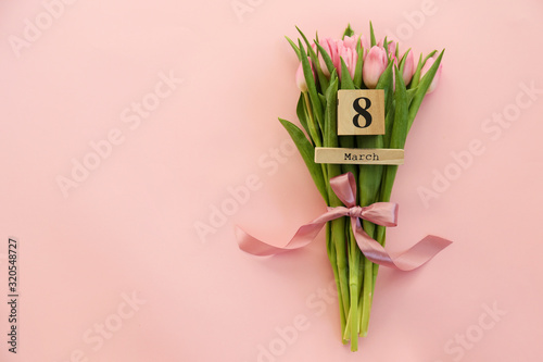Fototapeta Wooden cube calendar showing 8th of March date, the International women's day holiday with beautiful pink tulip flowers bouquet. Close up, copy space, background. Holiday greeting concept. obraz