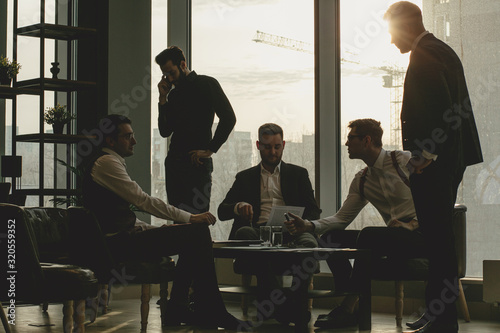Obraz business coworking of young caucasian bearded men in office gathered to discuss business ideas, share experiences and opinions, successful cooperation of enthusiastic business people - fototapety do salonu