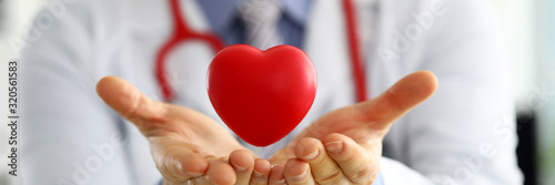 Male medicine doctor hands holding and covering red toy heart Fototapete