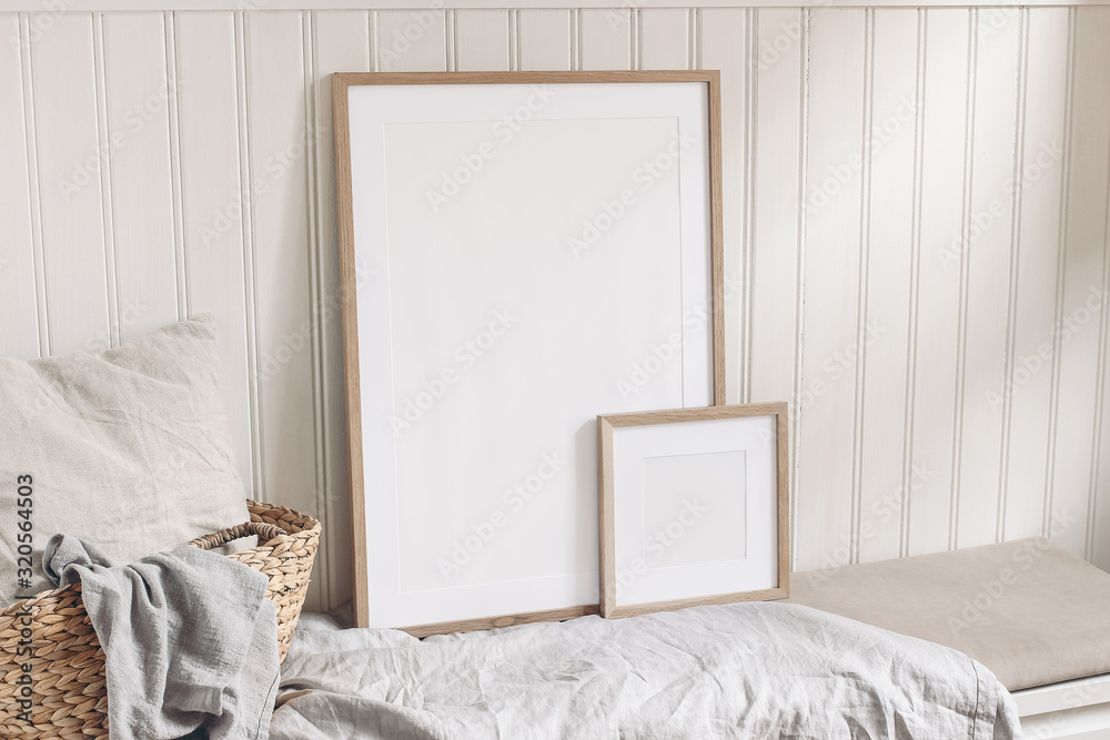 Fototapeta Portrait and square empty wooden frame mockups with straw basket and linen cloth. White beadboard wainscot wall paneling background. Scandinavian interior, home design. Art concept.