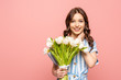 happy girl touching neck while holding bouquet of white tulips and smiling at camera isolated on pink