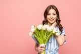 Fototapeta Tulipany - happy girl touching neck while holding bouquet of white tulips and smiling at camera isolated on pink