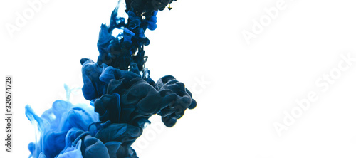 Mix of black and classic blue ink in water on an isolated white background with copy space.