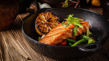 European Cuisine In Ukrainian Style. A Large Steak Of Red Salmon Fish, With Mushrooms, Asparagus, Cherry Tomatoes And Fried Lemon. Serving Meals In A Rustic Restaurant.