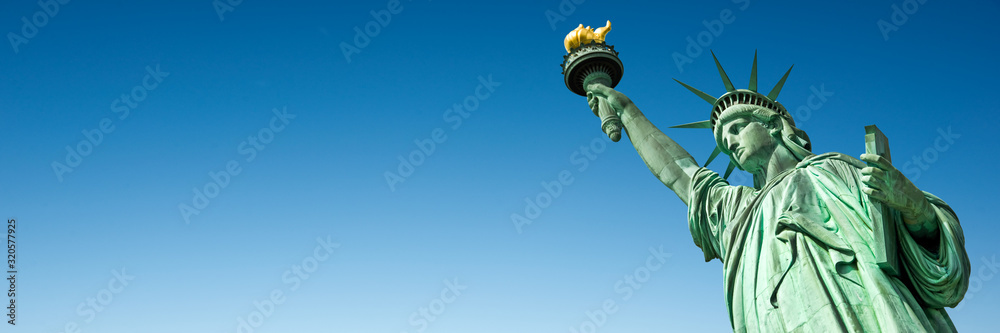 Fototapeta Statue of Liberty in New York, USA. Blue sky panoramic background with copy space