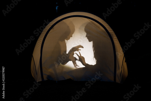 Photo Children making shadow puppets in a camping tent at night
