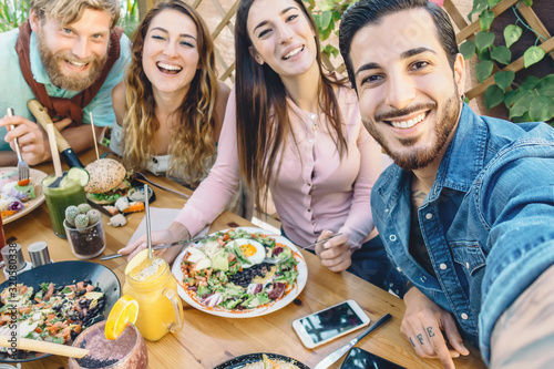 Photographie Happy friends taking selfie with mobile smartphone while lunching in coffee brun