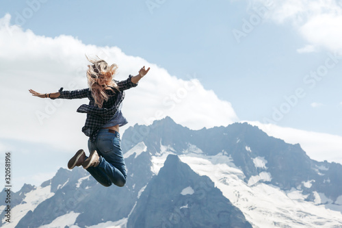 fototapeta na ścianę Woman hiker jumping on top of the mountain over blue skies