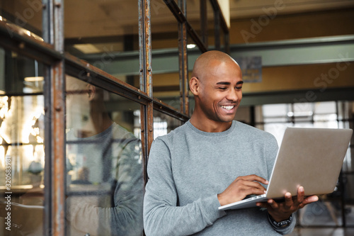 Photo Image of bald african american man holding laptop while working in office