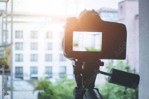 Surveillance and stalking concept: Camera with telephoto lens on tripod, observi Obraz na płótnie