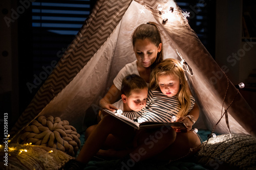 Fototapeta Mother with children sitting indoors in bedroom, reading a book. obraz