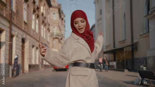 Amazing beauty arab woman dancing of happiness walking on the street in wonderful old city in sunny weather Wallpaper Mural