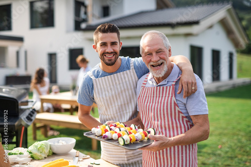 Obraz Portrait of father and son outdoors on garden barbecue, grilling. - fototapety do salonu