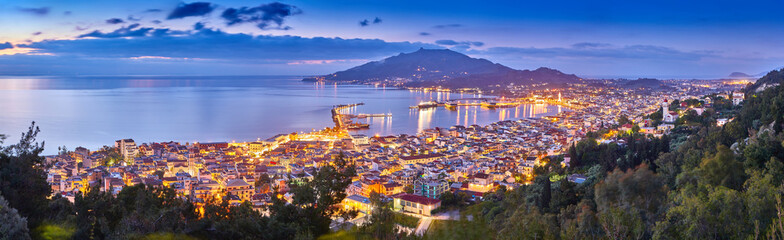 Panoramic city and port view on the island of Zakynthos, Greece. Incredibly romantic sunrise on Zakinthos. Amazing sunset view on Zante town with multicolored clouds. Street lights. Port with ferries