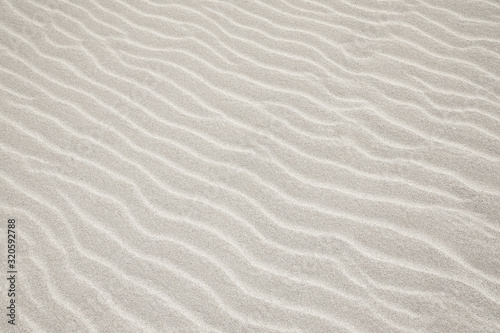White Sand dunes background texture. Beach and sand texture. Pattern of sand. Beautiful sand dune in sunrise in the desert. Steps on the beach sand.