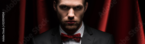 Photo panoramic shot of concentrated man in suit and bow tie in circus with red curtai