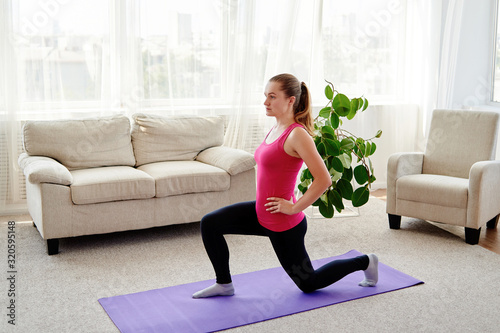 Fototapeta Young attractive woman doing lunge exercise at home, stretching legs