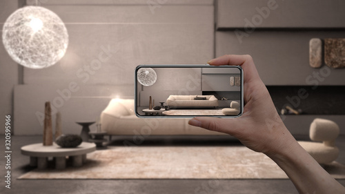 Obraz Hand holding smart phone, AR application, simulate furniture and interior design products in real home, architect designer concept, blur background, grunge lounge with plaster walls - fototapety do salonu