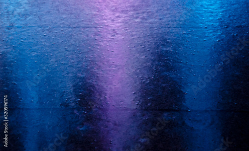 Fotografia Blurred neon city lights reflected in a puddle and raindrops during the rain (as