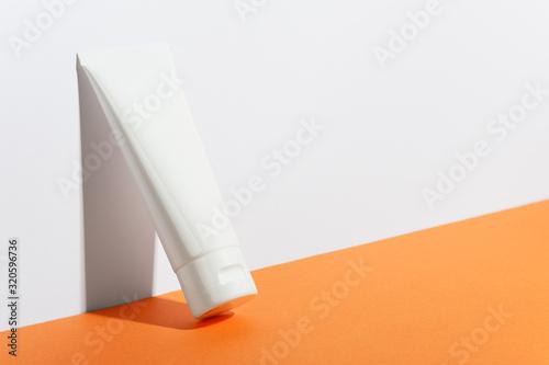 Cream tube on bright sunny orange background Canvas Print