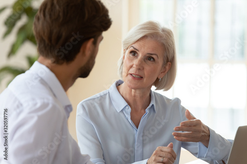 Poważni, różnorodni biznesmeni rozmawiają, omawiają pomysły na spotkaniu