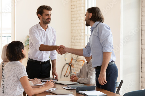 Photo Smiling businessman handshake male colleague at team meeting