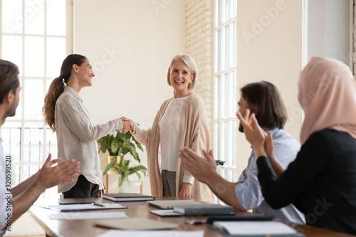 obraz PCV Smiling businesswoman handshake middle-aged employee greeting with employment