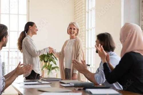 Uśmiechnięty bizneswomanu uścisku dłoni pracownika w średnim wieku powitanie z zatrudnieniem