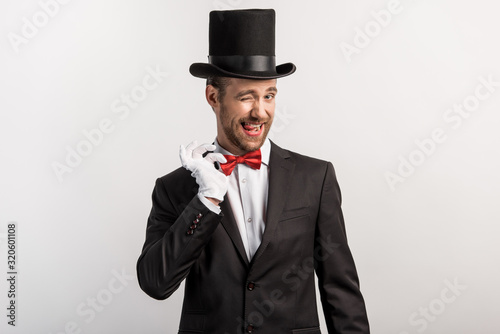 emotional magician winking and adjusting bow tie, isolated on grey Wallpaper Mural