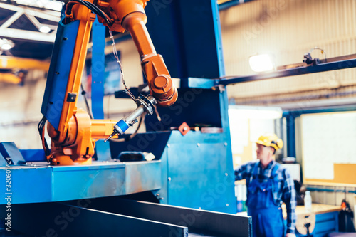 Photo Worker operating robotic arm to cut steel in a factory.