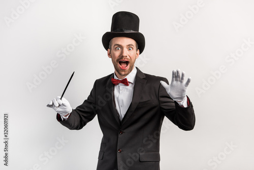 Photo excited magician in suit and hat holding wand, isolated on grey