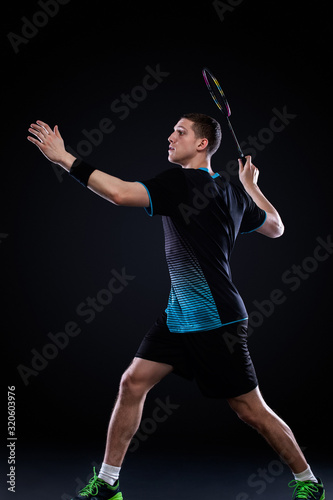 Badminton player in sportswear with racket and shuttlecock on black background Fotobehang