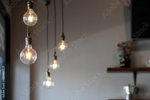 Leinwand Poster vintage light bulb hanging from ceiling for decoration in living room