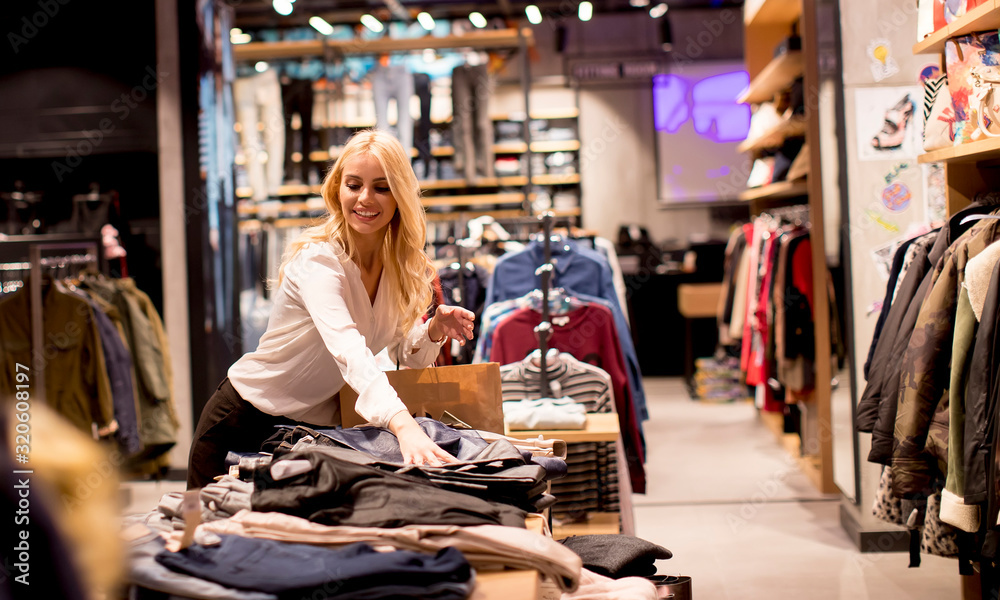 Fototapeta Beautiful young woman with shopping bags standing at the clothing store