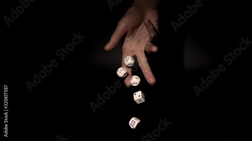 Fotografía Hand throwing gambling dice on  table, black background