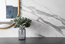 Artificial Plant In Glass Vase Compose With Gold Stainless Mirror Frame On Gray Spray-painted  Working Table With  Marble Wall In The Background With Copy Space /apartment Interior
