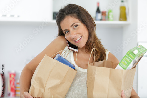 Fototapeta woman talking on cellphone while encumbered with shopping bags obraz