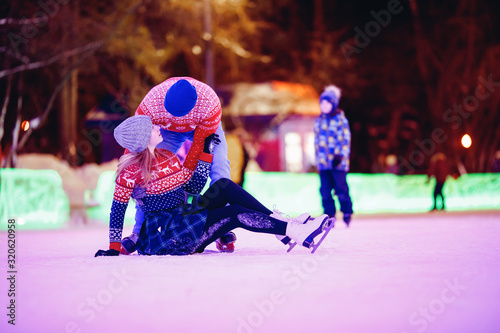 Young guy gets acquainted with girl on rink winter in ice skates, concept first Wallpaper Mural