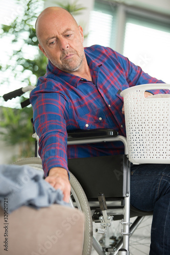 Fototapeta disabled man on wheelchair doing laundry obraz