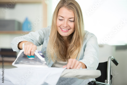 Fototapeta woman on wheelchair during ironing at home obraz