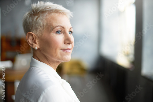 Close up profile shot of elegant short haired businesswoman wearing pearl earrings and stylish white blouse posing isolated in office interior, having pensive thoughtful look. Job, work and mature age