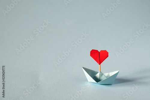 Fototapeta Valentine's day greeting card. Origami boat with heart flag on glitter blue background Romantic, Valentines day concept with space for text. obraz