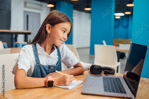 Pretty girl using a laptop computer at modern school. Canvas Print