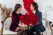 young woman and man sittihng on the couch and looking at each other while holding bouquet with red flowers in the focus