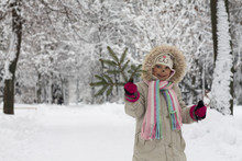 A Beautiful Little Girl With A Cat Face In Bright And Vibrant Clothes Is Holding A Green Pine Branch Of A Christmas Tree Against The Background Of A Snow Covered Park.