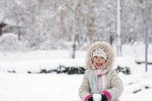 Beautiful Little Girl With A Cat Face In Bright And Bright Clothes Holding A Snowball Against The Background Of A Snow-covered Park