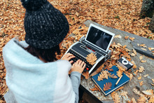 Unrecognizable Cropped Person Typing On A Vintage Typewriter With A Tablet Instead Of Paper In Autumn With Leaves Everywhere On A Stone Table In A Oak Forest