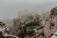 Destroyed Old Stone Castle With Fog With Walls And Stairs With Tower On Cloudy Day