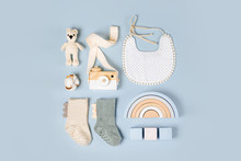Set Of Baby Stuff And Accessories For Boy On Light Blue Background. Cute Socks, Bib And Toys. Baby Shower Concept.  Fashion Newborn. Flat Lay, Top View